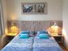 slaapkamer met een tweepersoons bed voorzien van 1 persoons matrassen
